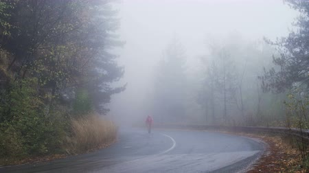 direkt : Alone young man lost in the fog, walking on empty road Stok Video
