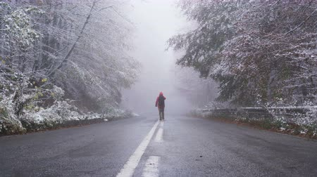 ethereal : Happy man walking on frozen asphalt road carrying his backpack in winter conditions