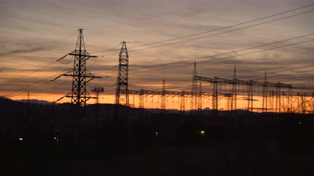 vezető : High-voltage power lines at sunset. Electricity distribution station