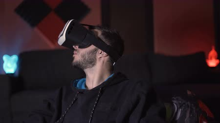invenção : Male gamer enjoying virtual reality wearing VR glasses, making gestures with his hand