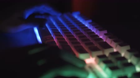 スペル : Close view of Esport athlete, gamer playing on RGB keyboard with colorful lights