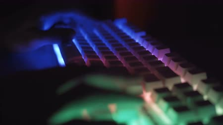 スペル : Side view of male hands working on keyboard with glowing keys 動画素材