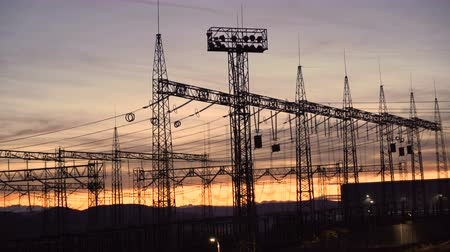 visão global : Distribution electric substation with power lines and transformers against beautiful sunset sky
