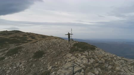 övgü : Male hiker standing on peak and victoriously raising arms rejoicing success