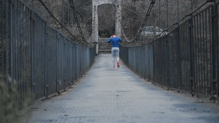 спринт : Strong male runner with big red headphones and blue shirt going for training, walking slow on metal bridge Стоковые видеозаписи
