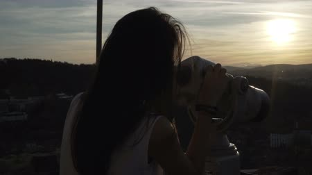 příloha : Girl with blown by the wind hair watches the sunset over Veliko Tarnovo with binocular