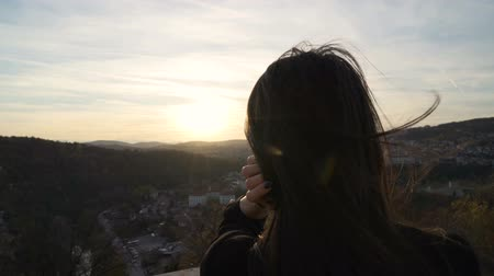 příloha : Girl with sunglasses enjoying the sunset over scenic landscape while wind blows into her hair Dostupné videozáznamy