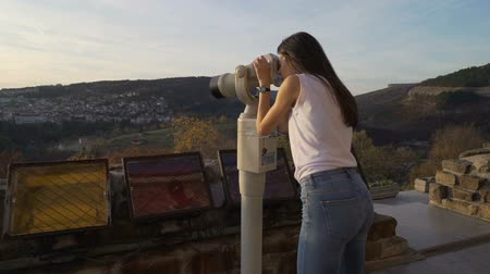 приложение : Female tourist, brunette girl with white shirt watching the panoramic view with binocular. Tsarevets, Veliko Tarnovo