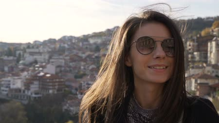 příloha : Beautiful smiling cheerful girl posing, wearing sunglasses and shined by the sunset