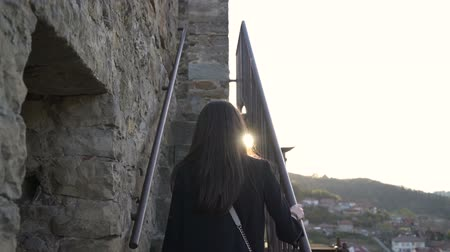 mítosz : Young woman climbing stairs in slow motion at medieval stronghold Tsarevets Stock mozgókép