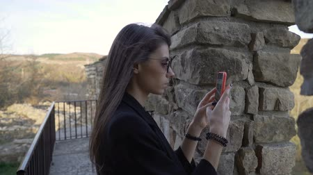 příloha : Side view of young beautiful brunette with sunglasses taking photos with and videos with smartphone Dostupné videozáznamy