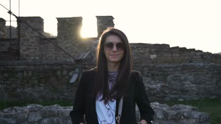 hayran olmak : Gorgeous brunette with sunglasses smiling and posing against medieval stronghold in the background