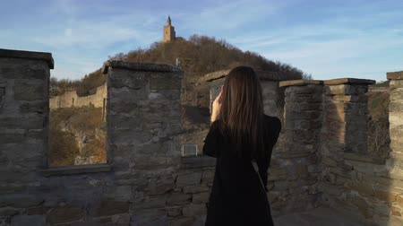 příloha : Brunette girl with black jacket enjoying sunny autumn day in old medieval stronghold called Tsarevets in Bulgaria Dostupné videozáznamy