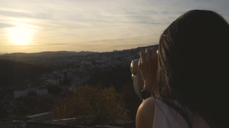 příloha : Close view of woman watching sunset over houses on the hills in Veliko Tarnovo using binocular