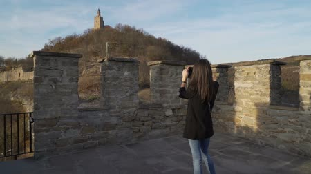 hayran olmak : Woman with black jacket taking pictures of old medieval stronghold in Veliko Tarnovo