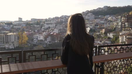 приложение : Brunette girl enjoying panoramic view over Veliko Tarnovo city at susnet Стоковые видеозаписи