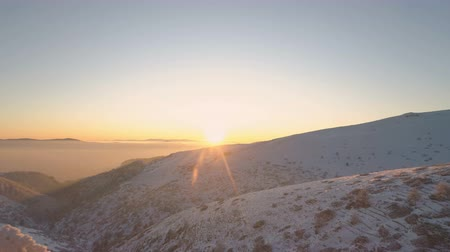 akşam vakti : Sunset trough frozen evergreen trees and snow covered mountains in Bulgaria Stok Video