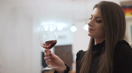 cheers : Woman in evening black dress tasting red wine at Christmas cocktail party Stock Footage