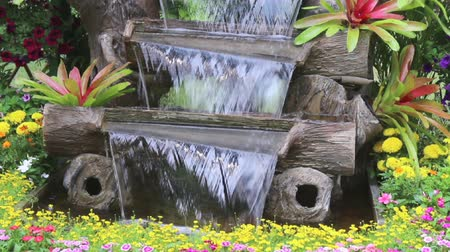 nemli : Footage waterfall flows and vivid flowers pot decoration in cozy home flower garden on summer.