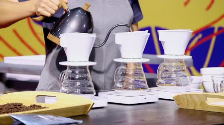part of clip : Footage showcase Drip coffee maker and Barista pouring hot water on ground coffee with filter. Stock Footage