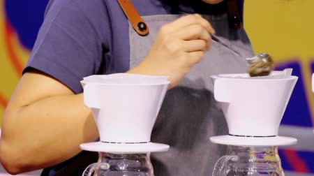 Footage showcase Drip coffee maker and Barista mix coffee beans into boiling water and stir.
