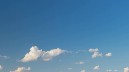 Formation and rapid movement of white clouds of different shapes in the blue sky in late spring at sunset. Stock Footage
