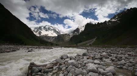 great video : Russia, time lapse. Movement of clouds and water flows in a stormy river in the Caucasus mountains in summer Stock Footage