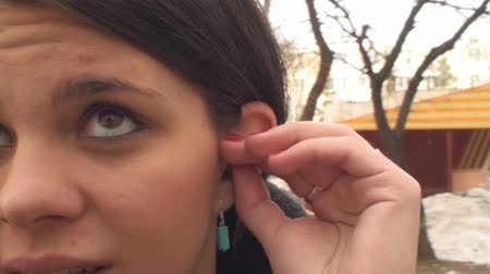 kulaklar : Young Female Pulls Out Her Hearing Aid From Her Left Ear Stok Video