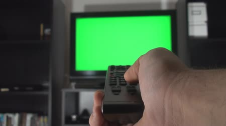 tv screen : Male Hand With TV Remote Switching Channels On A Green Screen TV Point Of View