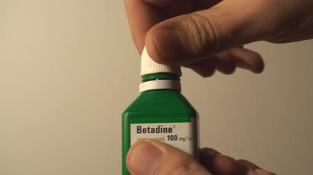 curativo : Man Opening A Bottle Of Betadine, Injury, Bandage, Hygiene, Side-Shot