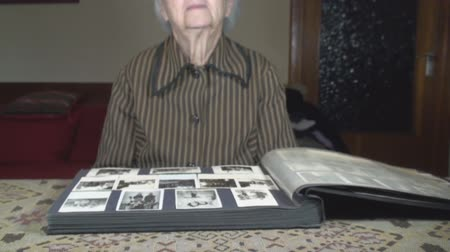 stary : Old Lady Going Through Family Photos Tilt-Shot Wideo