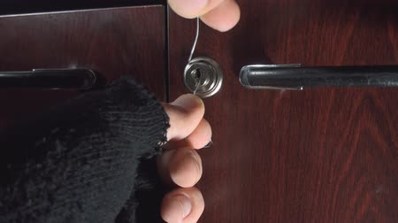 ladrão : Burglar Attempting To Open A Small Cabinet With Paper Clips Point Of View