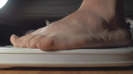 fogyás : Detail Of Feet Getting Onto The Weight Counter Side-Shot