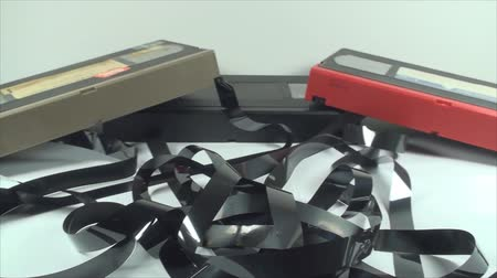 videocassette : Broken Cassettes, Loose Tape, Isolated On White, Retro, Media, Pan Shot Stock Footage