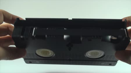 videocassette : Checking The Tape On An Old VHS Tape, Isolated On White, Vintage, Retro, Media