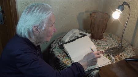 adresář : 98 Years Old Woman Writing A Phone Number In Address Book, Side Shot