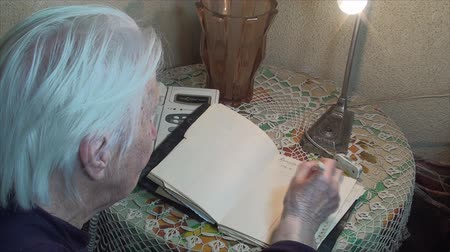 adresář : 98 Years Old Woman Writing A Phone Number In Address Book, Back Shot