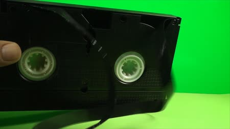 videocassette : Broken Cassette With Loose Tape On A Green Screen, Video, Chroma Key Stock Footage