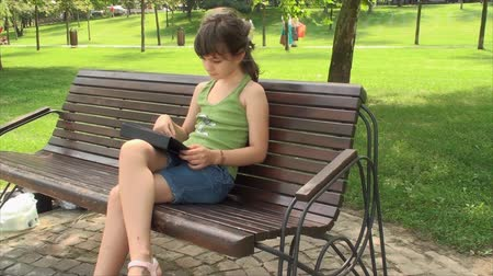 девчушки : Little Girl Play With Tablet Computer On A Bench In Park, Outdoors, Side Shot, Pan