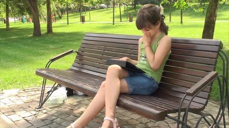 gry komputerowe : Little Girl Play With Tablet Computer On A Bench In Park, Outdoors, Side Shot, Pan