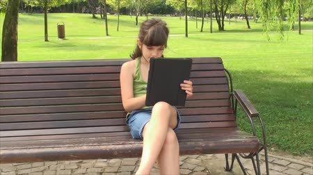 computerspel : Little Girl Play met Tablet PC op een bankje In het Park, buiten, Pan