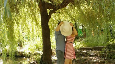parky : Young Couple Kissing Near A Willow In A Park Hiding Behind A Hat Dostupné videozáznamy