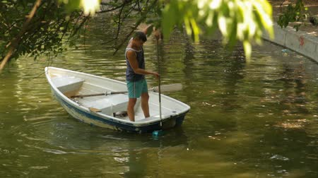 flutuador : Young Man On A Boat Cleaning A Lake, Pollution, Debris, Human Negligence