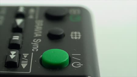 кнопка : Finger Touching The Stand By Button On A TV Remote, Extreme Close Up Side Shot