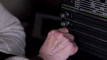 stáří : Detail Of Very Old Womans Hand Turning The Buttons Of A Vintage Radio, Pan Dostupné videozáznamy
