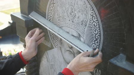 biblia : The hands of the artist draw the markings on the stone