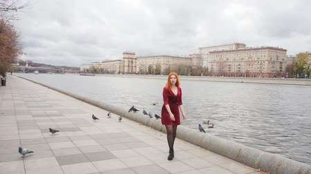 fulllength : Redhead girl dancing on the promenade and pigeons fly