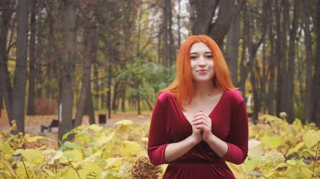 sexualita : Red-haired young girl posing in the park Dostupné videozáznamy