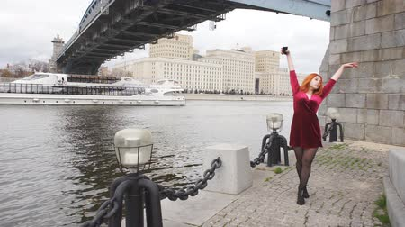 seductive : Dancing red-haired girl on the waterfront Stock Footage