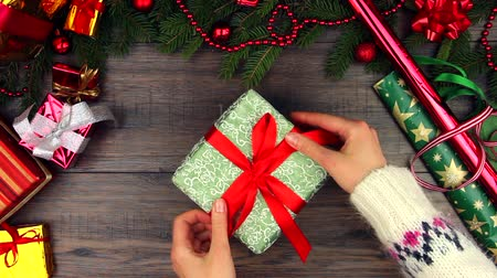dát : Hands of woman female adult wear fluffy winter sweater put give big New year green present on style wooden background with wrapping paper tinsel Christmas decorations balls tie correct red ribbon bow